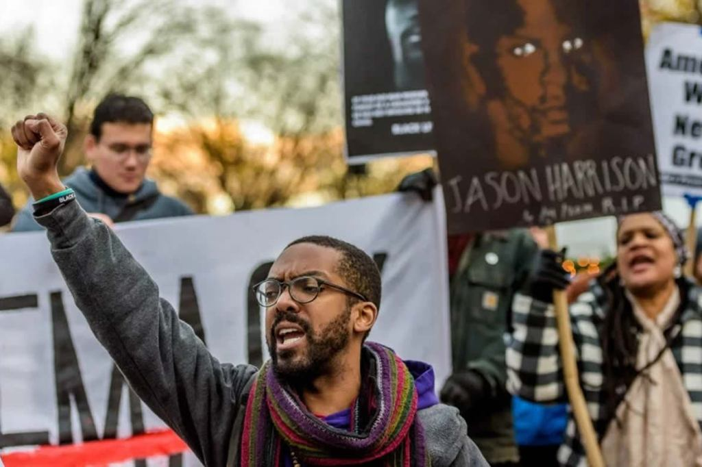 Image of a person raising their fist at a protest